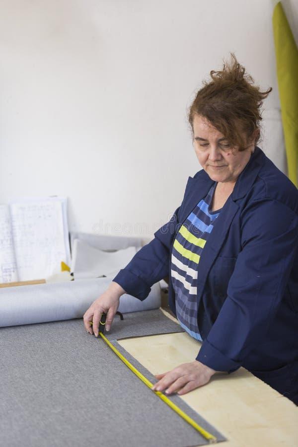 Ältere Frau in einer Möbelfabrik ist, markierend messend und ein graues Material für das Sofa mit einem Keil lizenzfreies stockbild