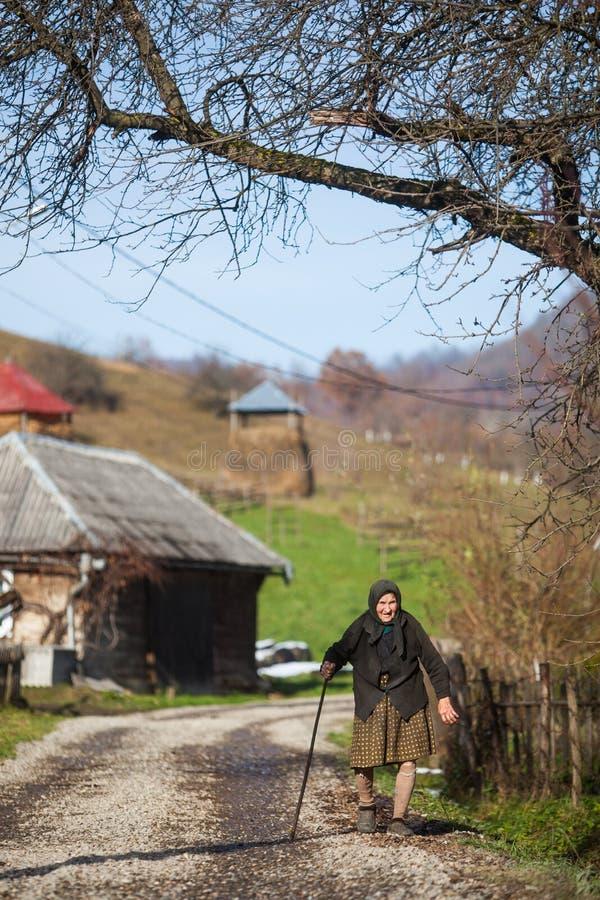Ältere Frau geht hinunter eine Straße in einem Dorf lizenzfreies stockbild