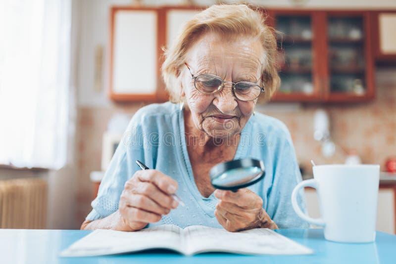 Ältere Frau genießt, ein Kreuzworträtsel zu lösen lizenzfreie stockfotografie