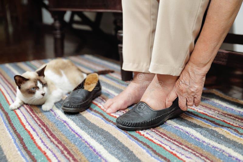 Ältere Frau geschwollen Füße, die auf Schuhe sich setzen stockbild