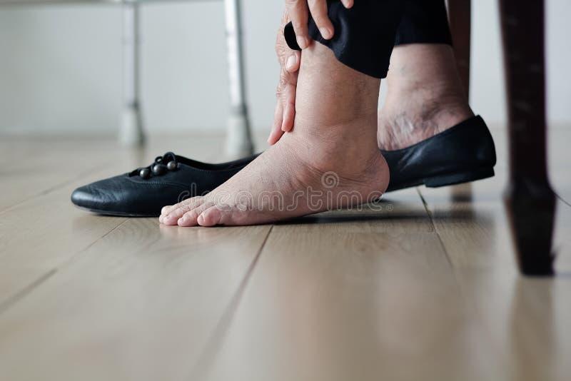 Ältere Frau geschwollen Füße, die auf Schuhe sich setzen stockfotografie