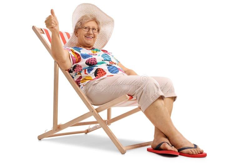 Ältere Frau gesetzt in einem Klappstuhl, der einen Daumen herauf Zeichen herstellt lizenzfreies stockbild