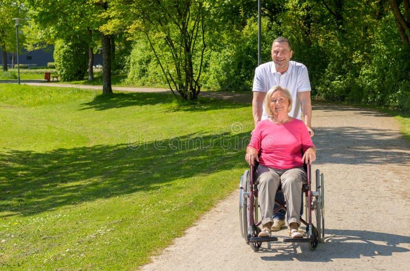 Ältere Frau gesetzt im Rollstuhl vom Ehemann lizenzfreie stockbilder