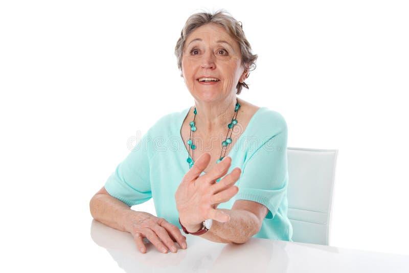 Ältere Frau hält einen Vortrag - die ältere Frau, die auf weißem Ba lokalisiert wird stockbild