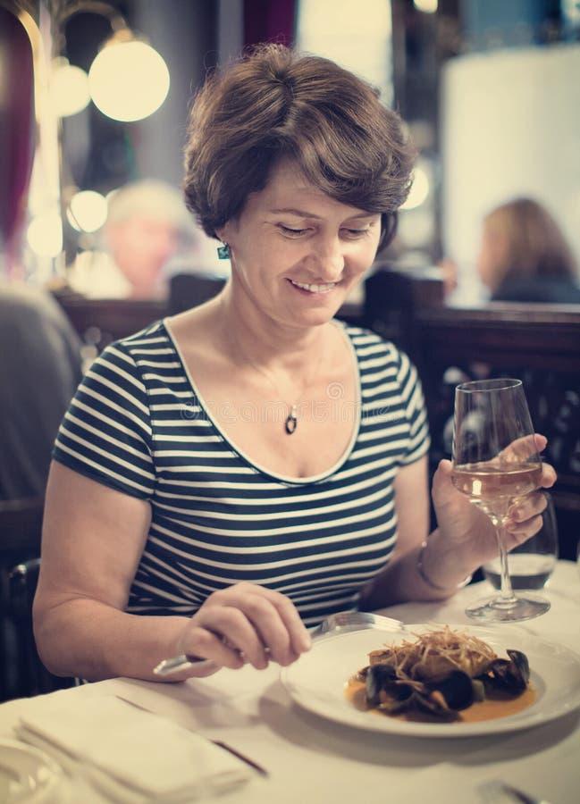 Ältere Frau hat Rest am Restaurant mit Weinglas lizenzfreie stockfotos