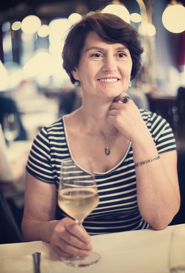 Ältere Frau hat Rest am Restaurant mit Weinglas lizenzfreies stockfoto
