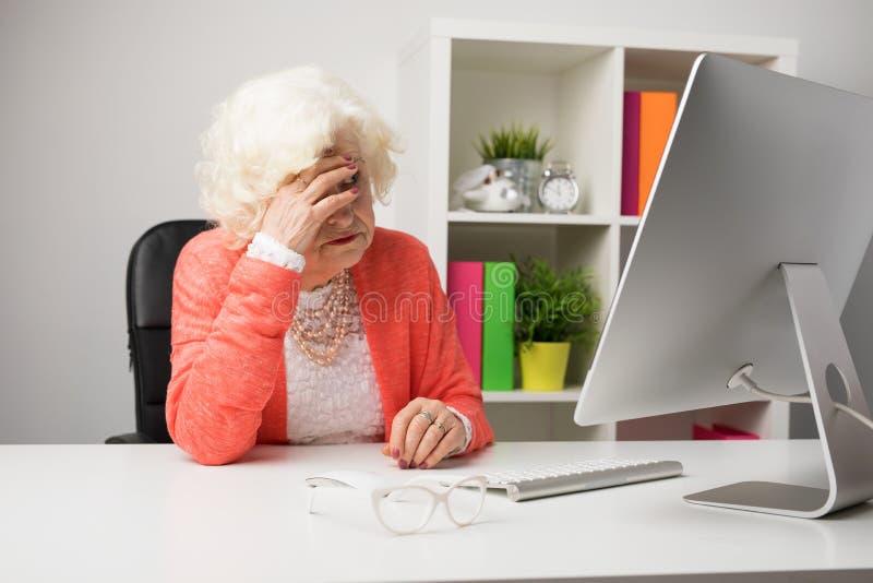 Ältere Frau im Büro, das Kopfschmerzen hat stockbilder