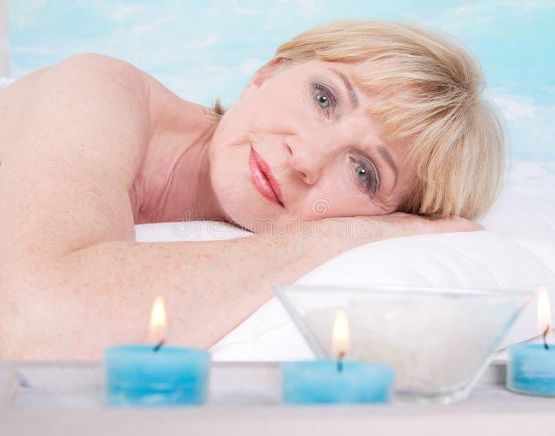 Ältere Frau im Badekurort mit Kerzen lizenzfreie stockbilder