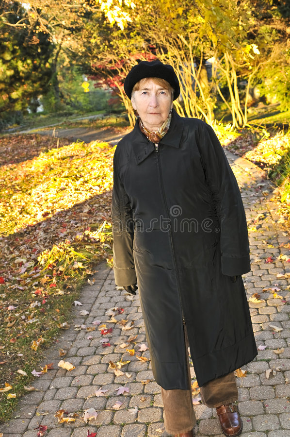 Ältere Frau im Fallpark stockfotos