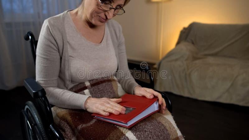 Ältere Frau im Fotobuch haltenen und lächelnden Rollstuhl, gute Gedächtnisse lizenzfreie stockfotografie