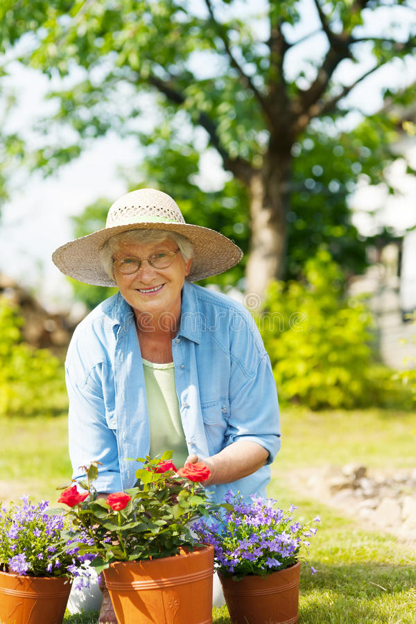 Ältere Frau im Garten stockbild