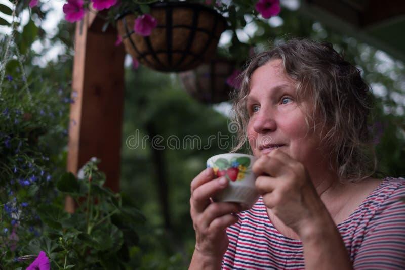 Ältere Frau im grünen Garten mit Blumen in den Händen lizenzfreie stockfotos