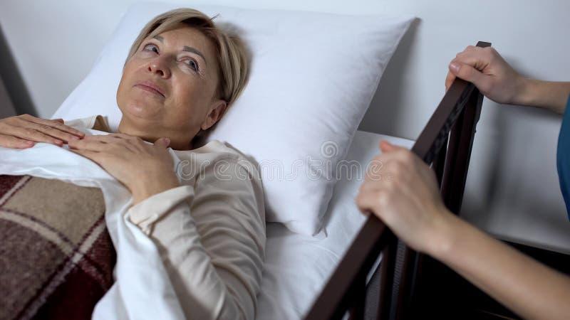 Ältere Frau im Krankenhausbett, das Doktor, hörend auf Empfehlungen betrachtet stockfoto