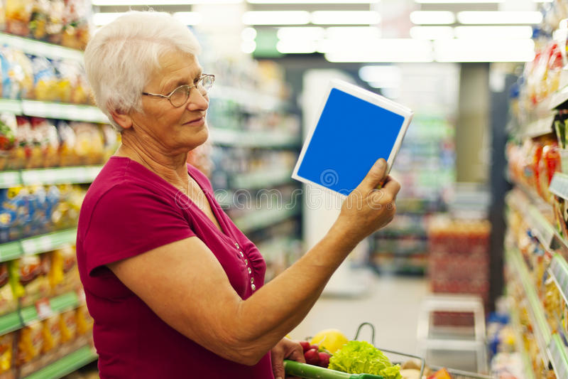 Ältere Frau im Lebensmittelgeschäftspeicher lizenzfreies stockfoto