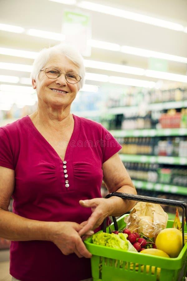 Ältere Frau im Lebensmittelgeschäftspeicher stockbilder