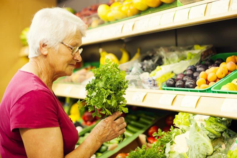Ältere Frau im Lebensmittelgeschäftspeicher lizenzfreie stockfotografie