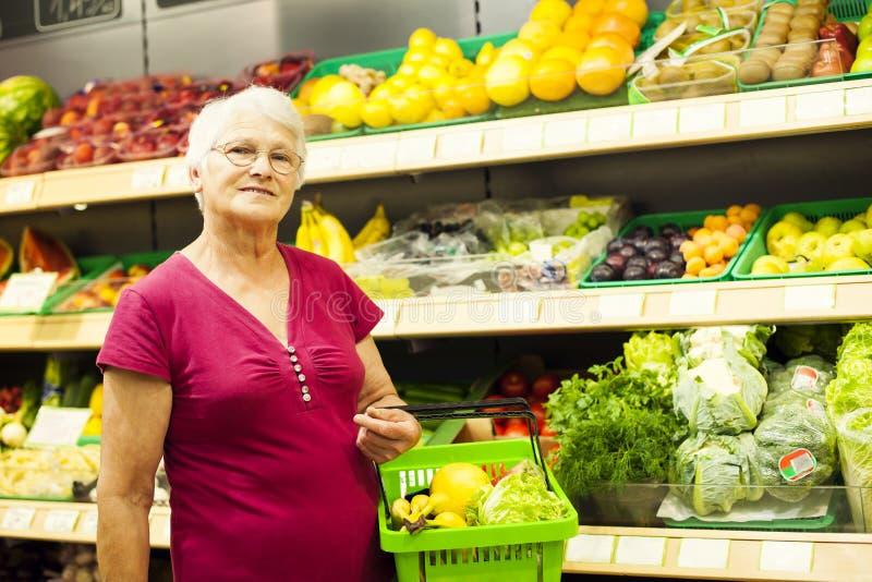 Ältere Frau im Lebensmittelgeschäftspeicher lizenzfreies stockbild