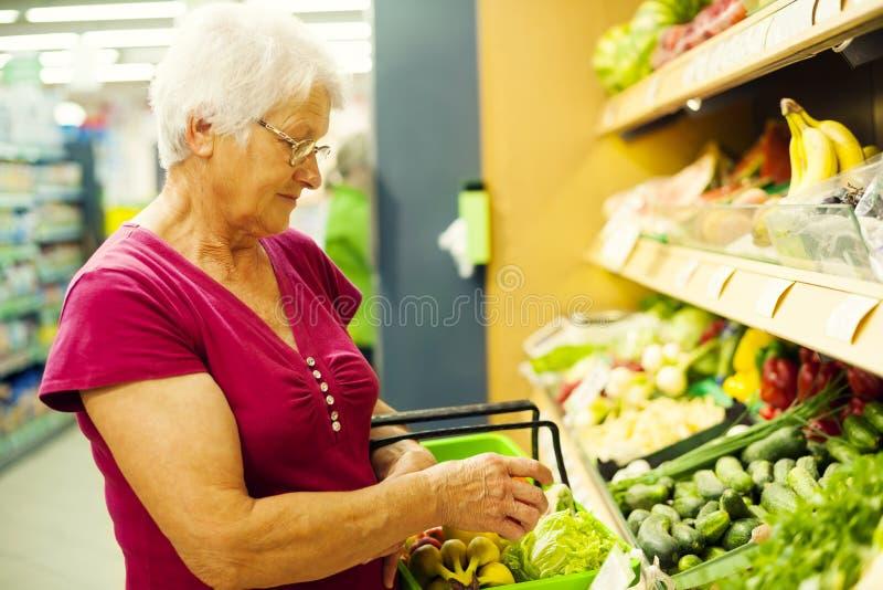 Ältere Frau im Lebensmittelgeschäftspeicher lizenzfreie stockbilder