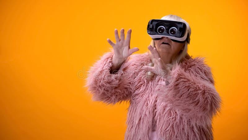Ältere Frau im lustigen Mantel und IN VR-Kopfhörer, die Videospiel, Spitzeninnovationen spielt stockbild