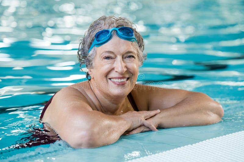 Ältere Frau im Pool stockbild