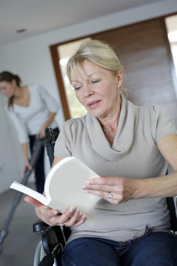Ältere Frau im Rollstuhl-Lesebuch lizenzfreie stockfotos