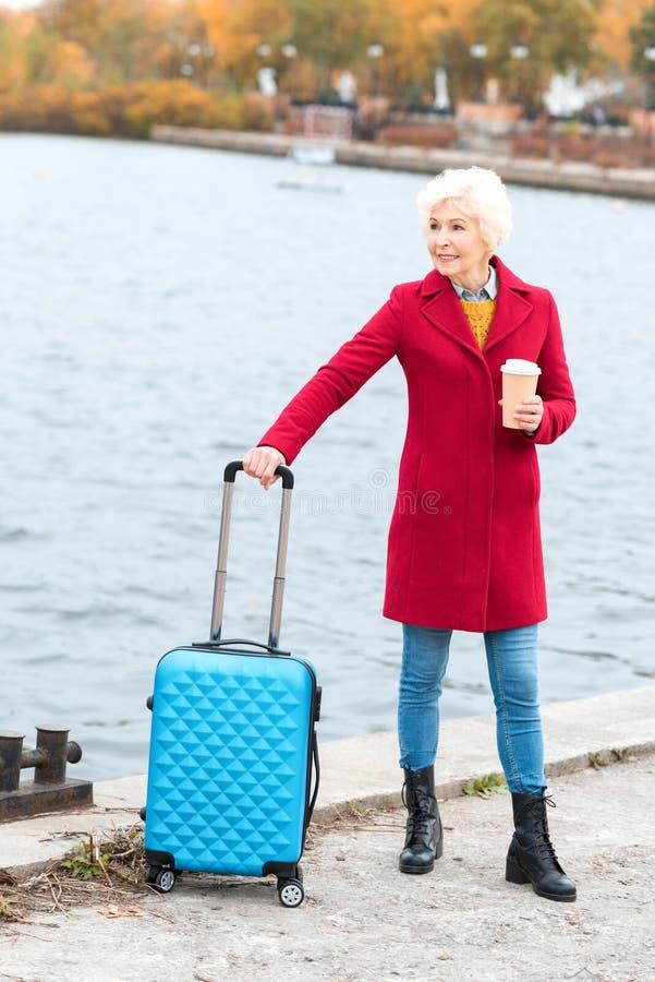 ältere Frau im roten Mantel mit Kaffee zum Mitnehmen und Koffer stockfotografie