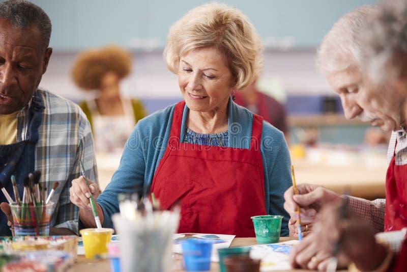 Ältere Frau im Ruhestand, die an Art Class In Community Centre teilnimmt stockfotografie