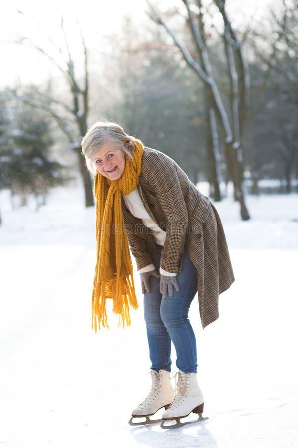 Ältere Frau im sonnigen Winternatureislauf stockfotografie