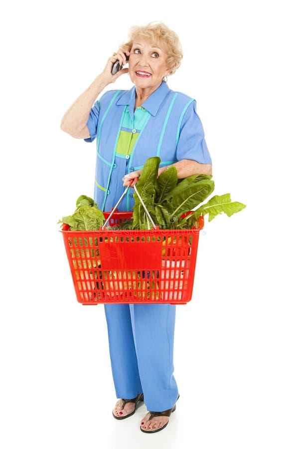 Ältere Frau kauft mit Mobiltelefon lizenzfreie stockfotografie