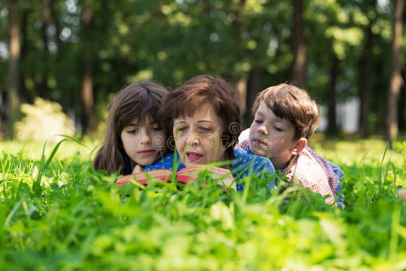 Ältere Frau, Mädchen und Junge liegen auf dem Rasen und lesen ein Buch gegen grünen Naturhintergrund Großmutter und Enkelkinder stockfotografie