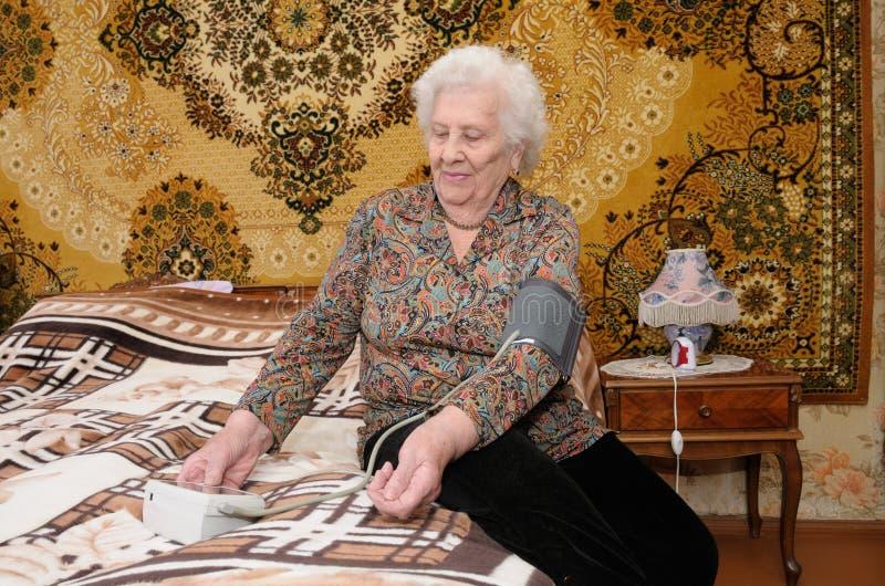 Ältere Frau misst ihren Blutdruck stockfotografie