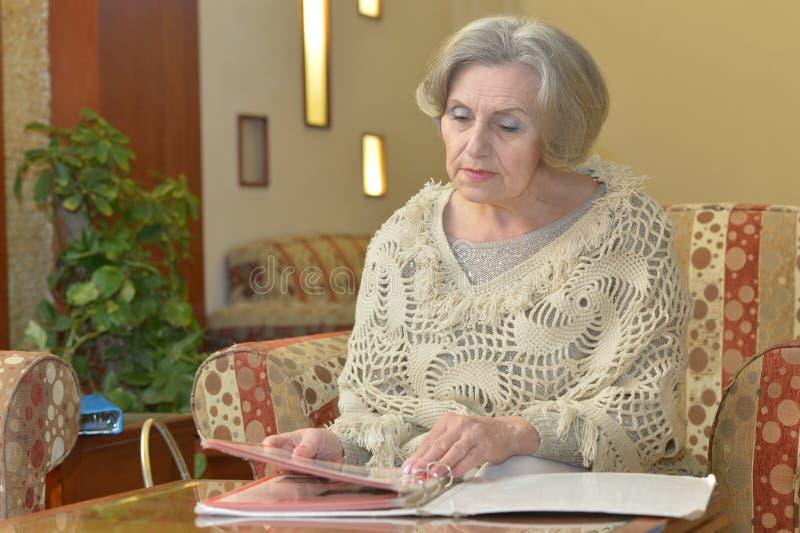 Ältere Frau mit Album zu Hause stockfotos