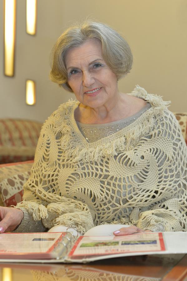 Ältere Frau mit Album zu Hause lizenzfreies stockfoto