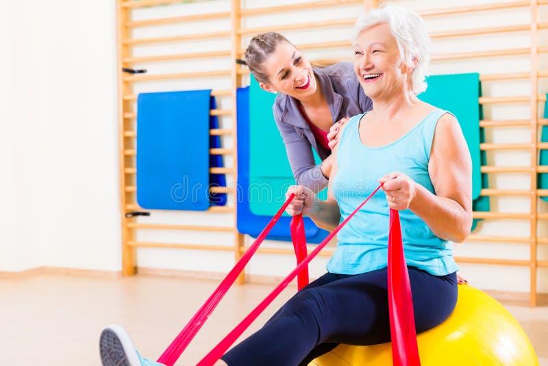 Ältere Frau mit Ausdehnungsband an der Eignung stockfoto