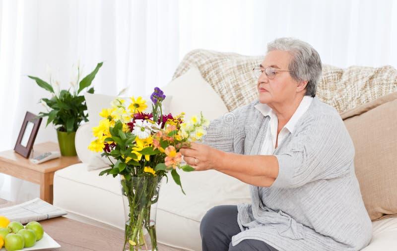 Ältere Frau mit Blumen stockbilder