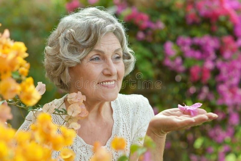 Ältere Frau mit Blumen lizenzfreie stockfotografie