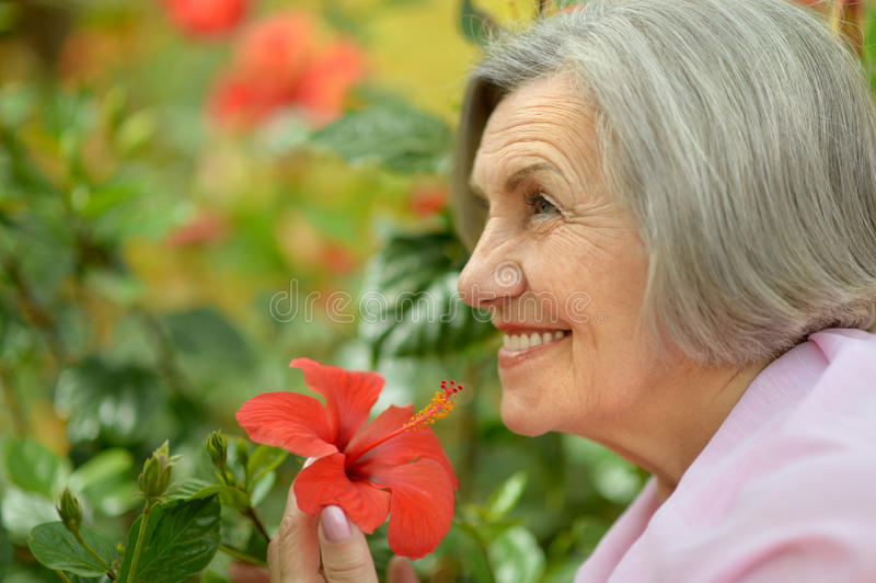 Ältere Frau mit Blumen stockfotografie