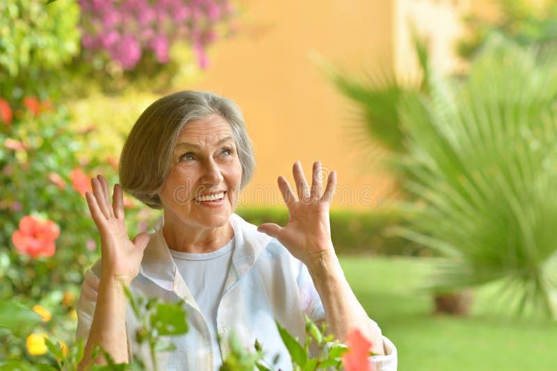 Ältere Frau mit Blumen lizenzfreie stockbilder