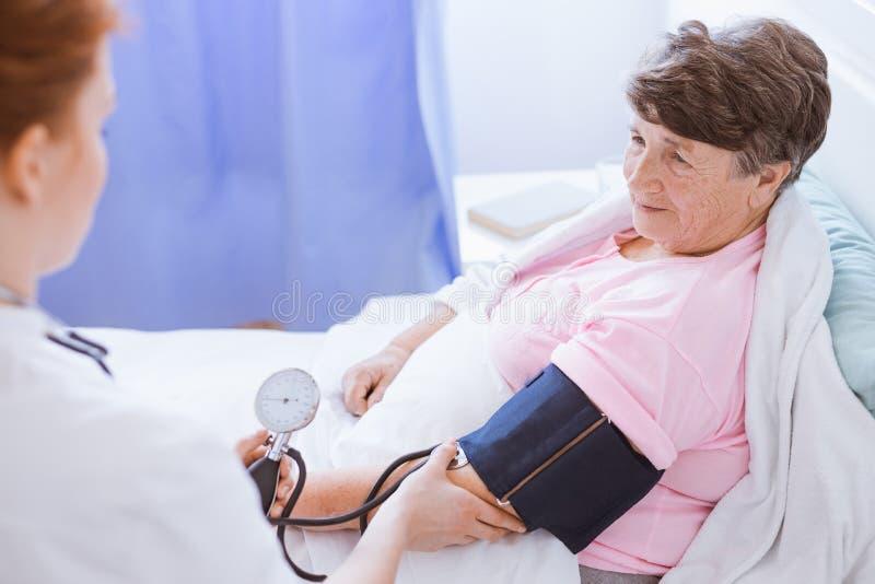 Ältere Frau mit Blutdruckmonitor auf ihrem Arm und jungen Internierten am Krankenhaus stockbild