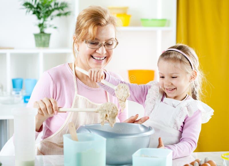 Ältere Frau mit dem kleinen Mädchen, das Teig macht stockfotos