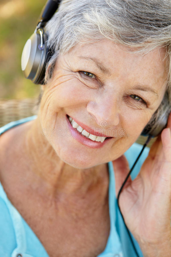 Ältere Frau mit dem Kopfhörerlächeln lizenzfreies stockbild