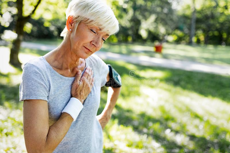 Ältere Frau mit dem Schmerz in der Brust, der unter Herzinfarkt während des Rüttelns leidet lizenzfreies stockfoto