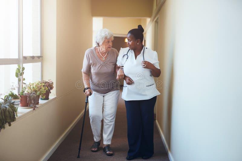 Ältere Frau mit dem Spazierstock, der von einer weiblichen Krankenschwester a geholfen wird stockfotografie