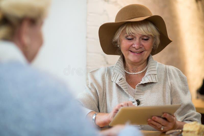 Ältere Frau mit dem Tablettenlächeln lizenzfreies stockbild