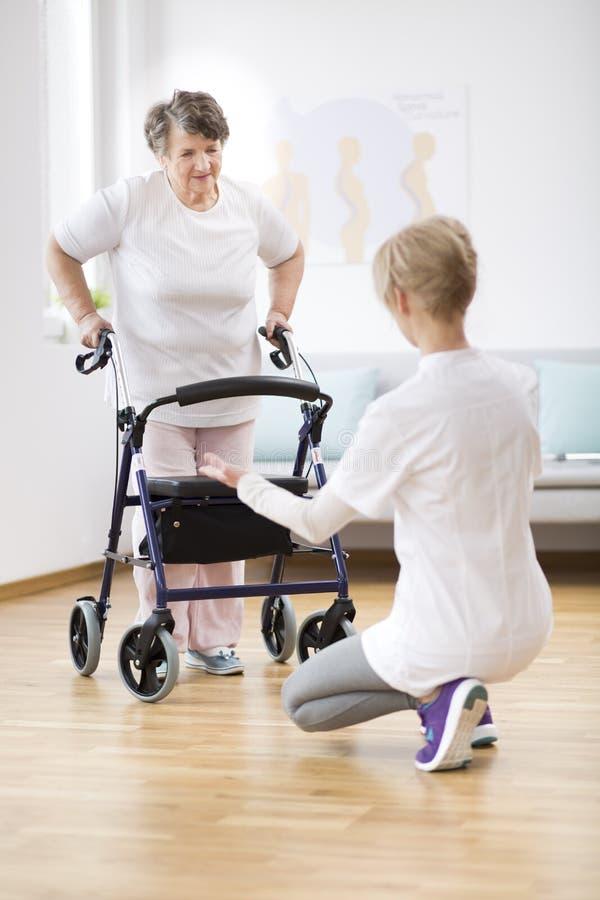 Ältere Frau mit dem Wanderer, der versuchen, wieder zu gehen und dem hilfreichen Physiotherapeuten, der sie stützt stockbild