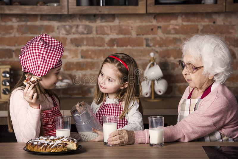 Ältere Frau mit den Enkelkindern, die Torte lächeln und schmecken lizenzfreie stockbilder
