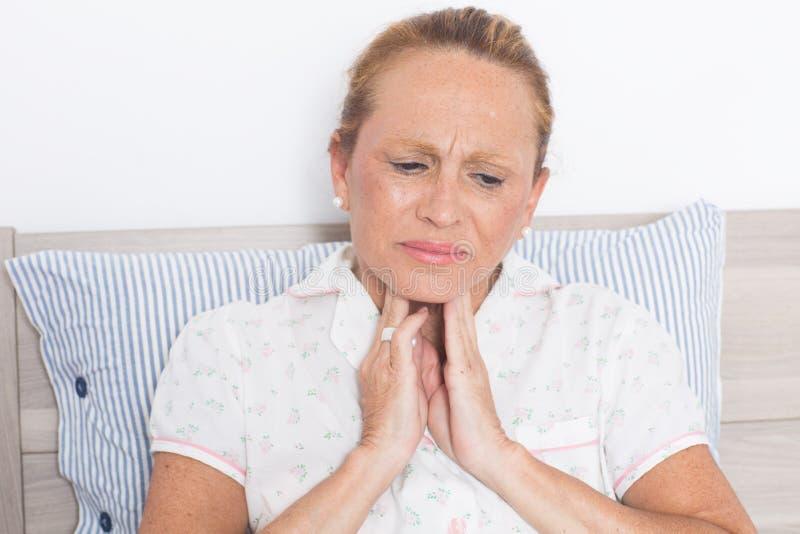 Ältere Frau mit den Halsschmerzen stockfotografie