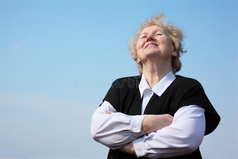 Ältere Frau mit den rised Händen schaut im Himmel lizenzfreies stockbild