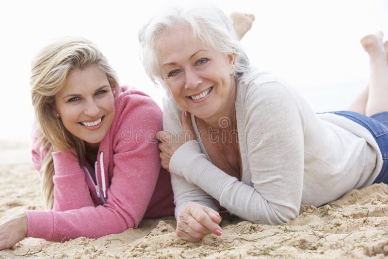 Ältere Frau mit der erwachsenen Tochter, die auf Strand sich entspannt stockfoto