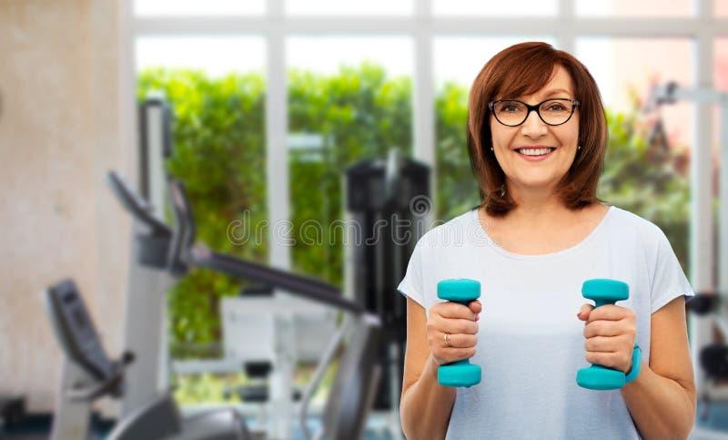Ältere Frau mit Dummköpfen trainierend in der Turnhalle stockbilder
